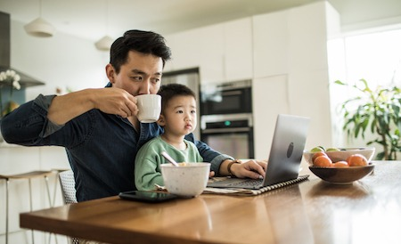 Father multi-tasking with young son (2 yrs) at kitchen table