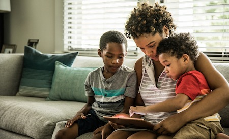 Single mother using tablet with young sons on couch